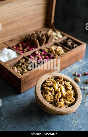 rustic wooden box full of oriental nuts, placed on gray table with wooden bowl full of walnuts - Stock Photo