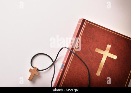 Bible on the side of a white table with cross-shaped wooden pendant. Top view - Stock Photo