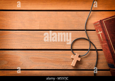 Brown leather cover of a Bible with cross-shaped wooden pendant on wooden slatted table. Top view - Stock Photo