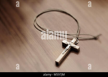 Closeup of crucifix on a wooden table. Elevated view - Stock Photo