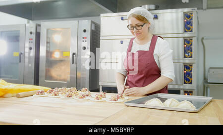 Adult woman in glasses bakes cakes in the bakery - Stock Photo