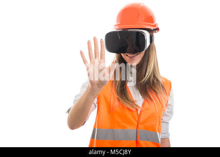 Attractive happy architect wearing vr glasses trying to touch something imaginary - Stock Photo