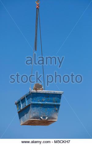 Construction crane lifting rubbish Skip hanging - Stock Photo