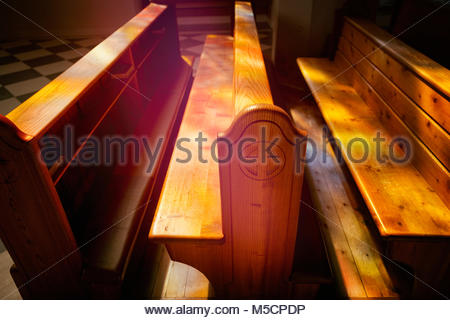 Interior church pew chapel stained glass window - Stock Photo