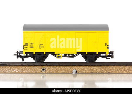 Yellow boxcar of an electric model train on the rails - Stock Photo
