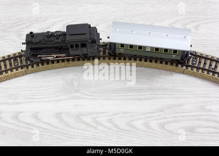 Model electric train formed by a vintage steam locomotive and a green passenger car on the rails over a wooden texture - Stock Photo