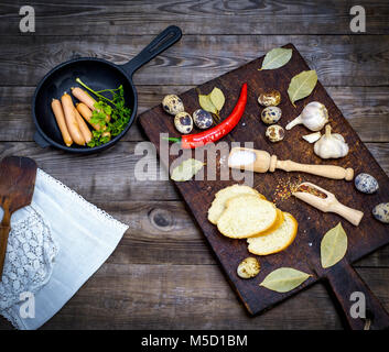 sausages in a black round cast-iron frying pan and raw quail eggs on a gray wooden table, top view - Stock Photo