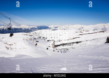 Lindars Nord two person chairlift carrying skiers to Tetes des Lindars, Flaine, Haute Savoie, Rhone-Alpes, France, - Stock Photo