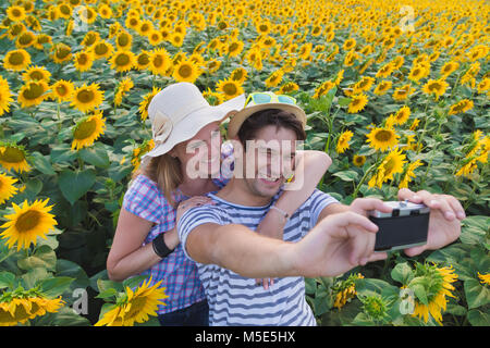 Young heterosexual couple taking selfie in sunflower field by using retro vintage film camera. Love and summertime - Stock Photo