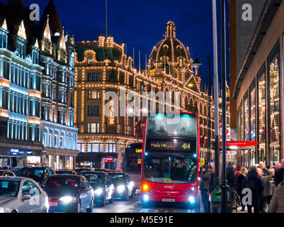 KNIGHTSBRIDGE Harrods department store at winter dusk with lit 'Sale' sign shoppers red bus and busy traffic Brompton - Stock Photo