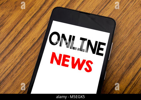 Word, writing handwriting Online News. Business concept for Online Newspaper Article Written on mobile phone, wooden - Stock Photo