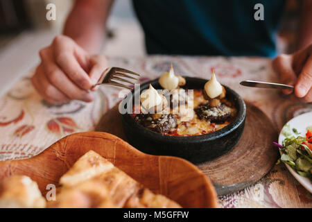 Man's hands holding cutlery - preparing to eat dish with mushrooms at table in cafe - Stock Photo