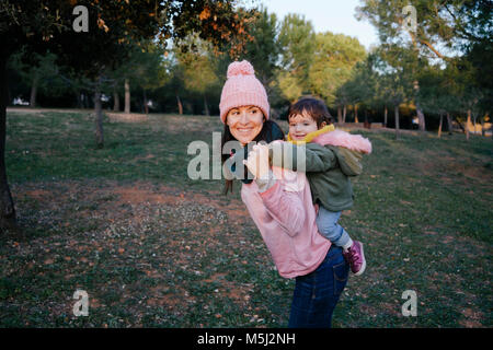 Happy mother carrying little daughter piggyback on a meadow - Stock Photo
