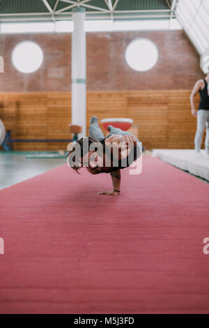 Young man doing acrobatic exercise in gym - Stock Photo