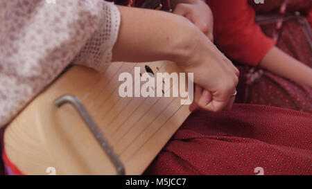 Gusli - woman in Russian folk costume playing vintage musical instrument - Stock Photo
