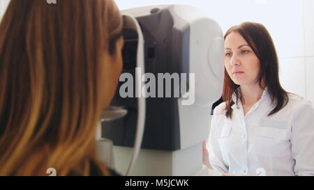 Ophthalmology clinic - optometrist checks patient's vision by modern electronic machine - Stock Photo