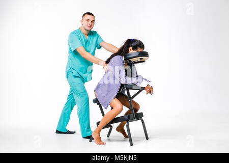 Theme massage and office. Male therapist with blue suit doing back and neck massage for young woman worker, business - Stock Photo