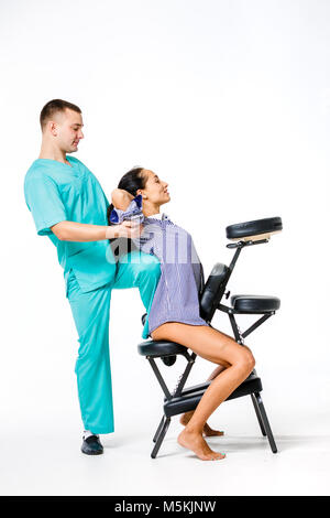 Theme massage and office. young male therapist in blue suit doing back massage with his knee braced in the spine - Stock Photo