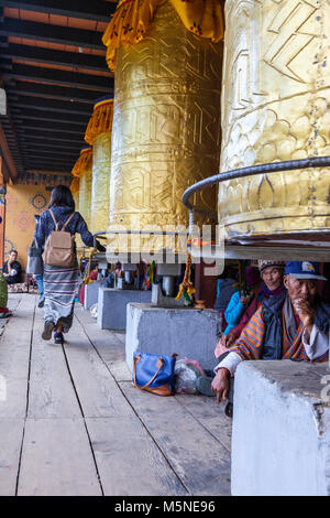 Thimphu, Bhutan.  Young Woman Turning Prayer Wheels at the National Memorial Chorten while Others Sit Underneath. - Stock Photo