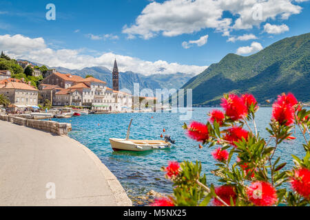 Historic town of Perast located at world-famous Bay of Kotor on a beautiful sunny day with blue sky and clouds in - Stock Photo