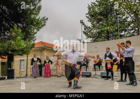 Arsos, Cyprus - October 8, 2017:  Cypriot dancer performing in traditional costumes with other dancers clapping. - Stock Photo