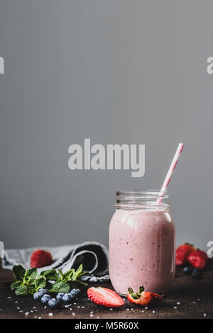 Pink strawbery smoothie in jar with drinking straw on grey background. Copy space for text, toned image. Healthy - Stock Photo
