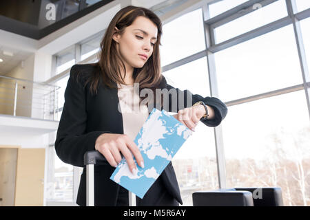 Waist up portrait of beautiful businesswoman checking time and holding airplane tickets while waiting for flight - Stock Photo