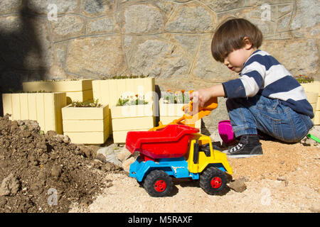 little three year old boy playing in the sand with a digger and dump truck. - Stock Photo