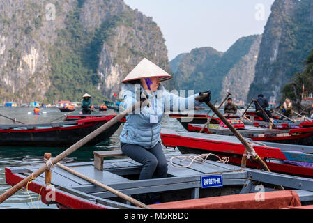 Vietnamese woman wearing traditional bamboo conical hat in a rowing boat to ferry passengers around the Cua Van - Stock Photo