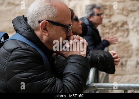 Jerusalem, Israel. 26th February, 2018. Worshippers pray outside the closed doors of the Church of the Holy Sepulchre - Stock Photo