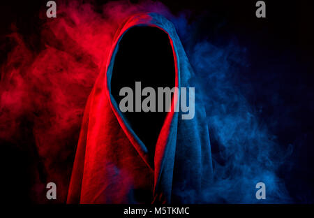 mysterious dark silhouette in hood hidden by colorful smoke on black background - Stock Photo