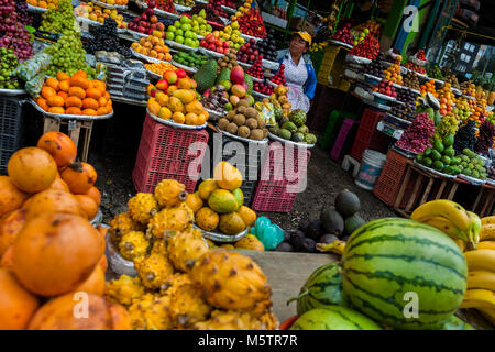 A Colombian vendor sits behind the piles of fruits at the market of Paloquemao in Bogotá, Colombia. - Stock Photo