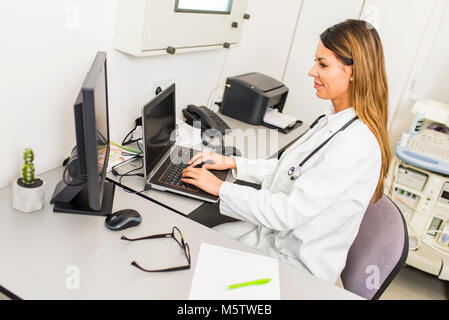 Portrait of young female doctor working on compute - Stock Photo