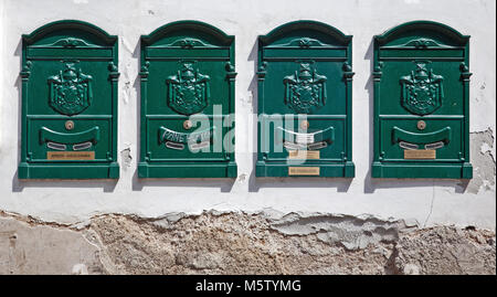 A row of four old green mailboxes on the wall of an apartment block in Sorrento, Italy. - Stock Photo