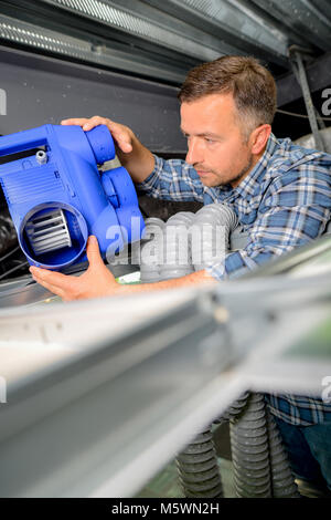 Man installing a new air conditioning unit - Stock Photo