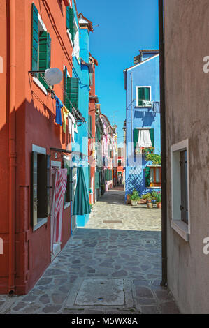 Overview of colorful terraced houses and clothes hanging in an alley on sunny day in Burano, a gracious little town - Stock Photo