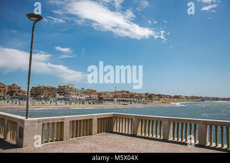 View in the foreground of marble pier, with the beach and the city of Ostia on a sunny day. A seaside resort and - Stock Photo