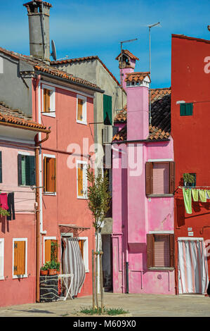 Burano, Italy - May 08, 2013. Overview of colorful terraced houses on sunny day in Burano, a gracious little town - Stock Photo