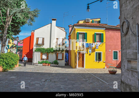 Burano, Italy - May 08, 2013. Overview of colorful terraced houses in an alley on sunny day in Burano, a gracious - Stock Photo
