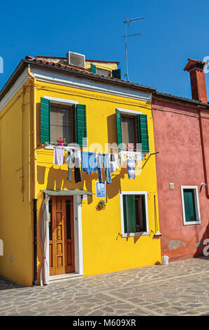 Burano, Italy - May 08, 2013. View of colorful terraced houses and clothes hanging in an alley on sunny day in Burano, - Stock Photo