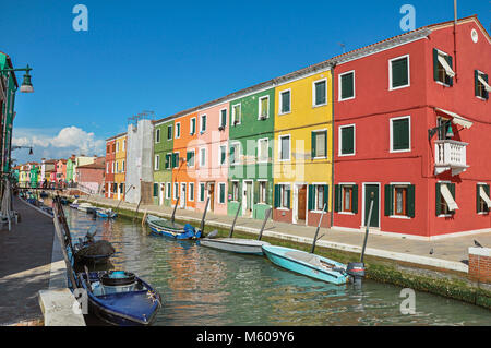 Burano, Italy - May 08, 2013. View of colorful buildings, people and boats in front of a canal at Burano, a gracious - Stock Photo