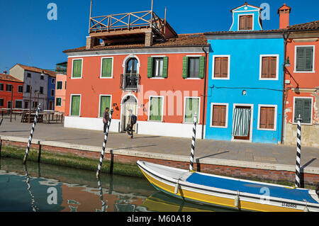 Burano, Italy - May 08, 2013. Colorful buildings, people and boats in front of a canal at Burano, a gracious little - Stock Photo