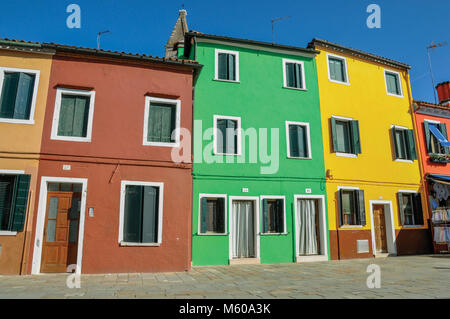 Burano, Italy. Overview of colorful terraced houses in alley on a sunny day in Burano, a gracious little town full - Stock Photo