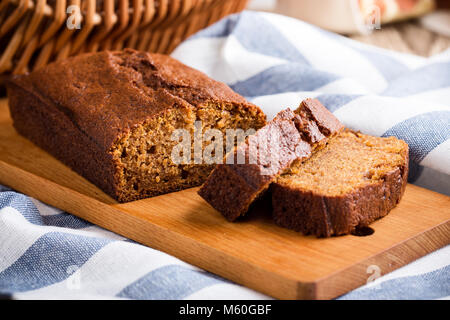 Homemade freshly baked pumpkin cake on rustic wooden board, sliced and ready to eat - Stock Photo