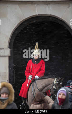 Whitehall, London, UK. 27th Feb, 2018. A mounted Life Guard on sentry duty at the entrance to Horse Guards as snow - Stock Photo