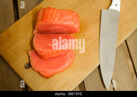 Sliced salmon fillet on cutting board - Stock Photo