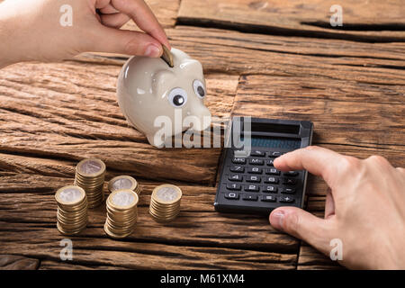 Close-up Of Person Calculating On Calculator With Stack Of Coins And Piggy Bank - Stock Photo