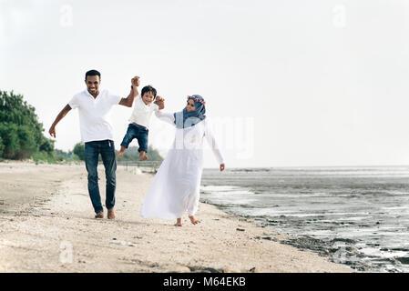 happy family having fun at muddy beach located in pantai remis,Selangor,Malaysia. Family concept - Stock Photo
