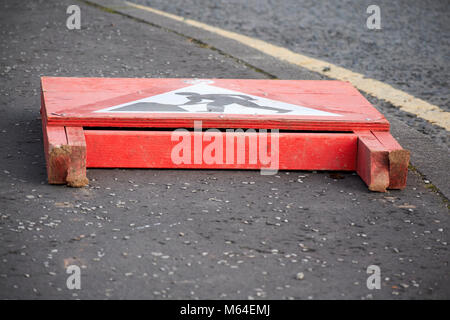 roadworks temporary roadworks sign fallen over by the side of the road in the uk - Stock Photo