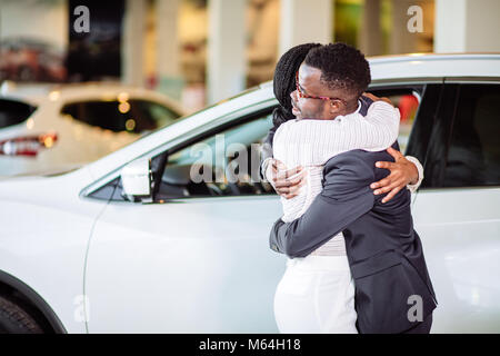 Couple collecting new car from salesman on lot - Stock Photo